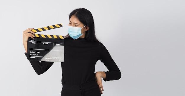 Mulher asiática usa máscara facial ou máscara médica e prensa para as mãos em claquete preto