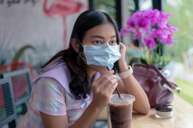 Mulher asiática usa máscara protetora para beber chocolate gelado com canudo sob a máscara facial em um café moderno