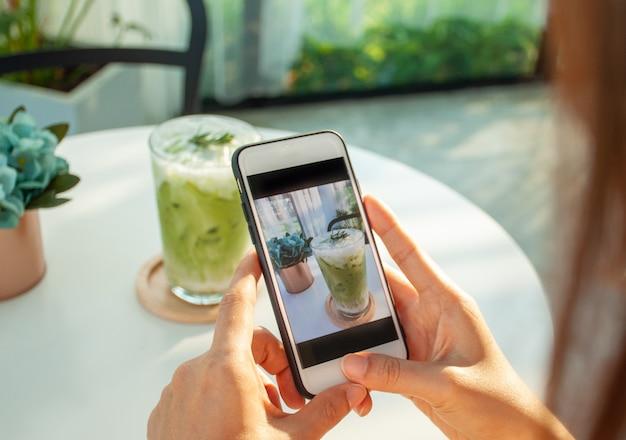 Mulher asiática usa um smartphone para tirar fotos de chá verde em um café