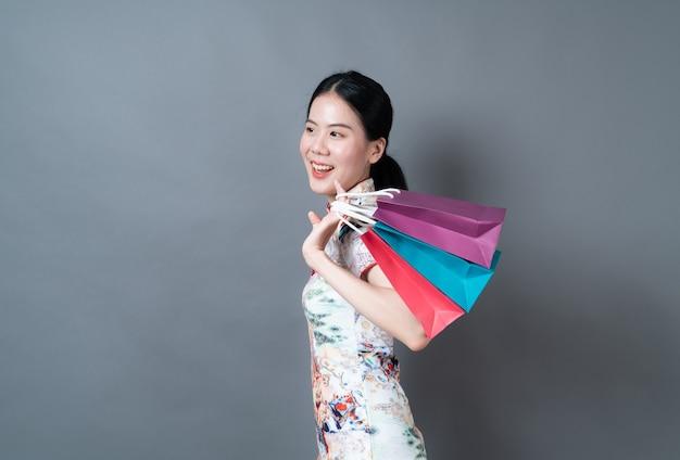 Mulher asiática usa vestido tradicional chinês com a mão segurando uma sacola de compras no fundo cinza