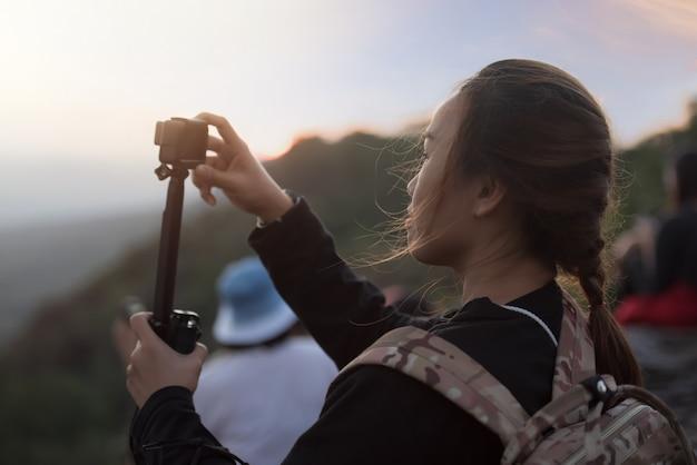 Mulher asiática, usando a câmera de ação durante a viagem de viagem