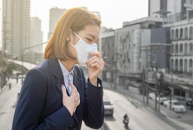Mulher asiática usando a máscara de proteção respiratória n95 contra a poluição do ar pm2.5 e dor de cabeça sufocar