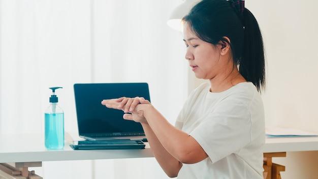 Mulher asiática usando álcool gel desinfetante para as mãos lavar a mão antes de abrir o tablet para proteger o coronavírus. mulheres pressionam o álcool para limpar a higiene quando o distanciamento social fica em casa e o tempo de quarentena