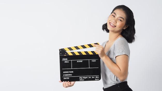 Mulher asiática usando aparelho e lentes de contato com as mãos segurando uma claquete preta sobre fundo branco
