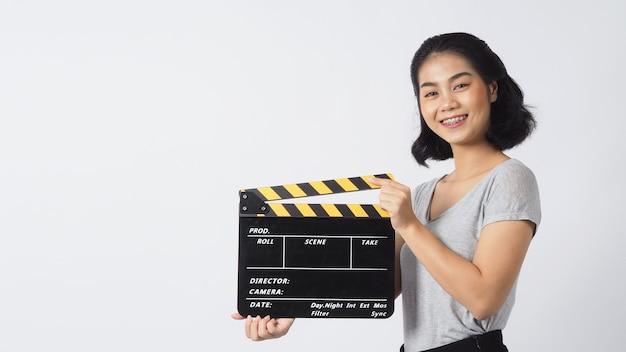 Mulher asiática usando aparelho e lentes de contato. sua mão está segurando um claquete preto ou uma tela de cinema para uso em produção de vídeo, cinema, indústria do cinema em fundo branco. ela tem pele bronzeada.