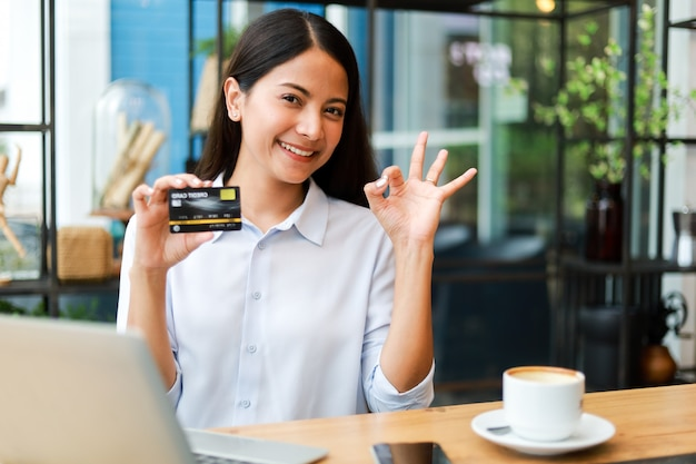 Mulher asiática usando cartão de crédito, compras on-line no café café
