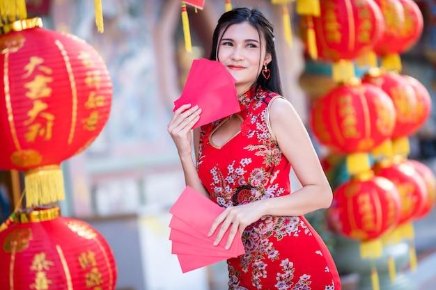 Mulher asiática usando cheongsam chinês tradicional vermelho, segurando envelopes vermelhos