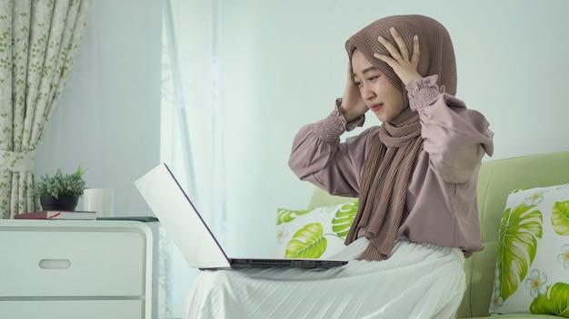 Mulher asiática usando hijab fica tonta com a tela do laptop