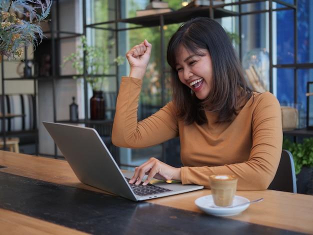 Mulher asiática usando laptop no café café