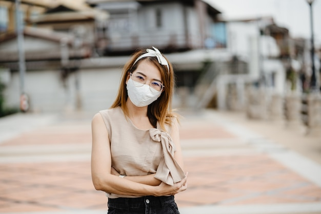 Mulher asiática usando máscara branca para proteger o vírus corona, máscara protetora antivírus com padrão para impedir o coronavírus covid-19