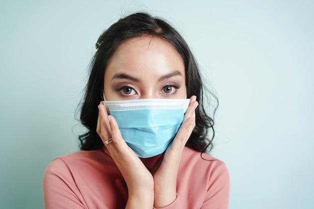 Mulher asiática usando máscara cirúrgica para se proteger do vírus covid-19 e doenças
