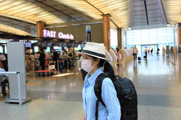 Mulher asiática usando máscara de carbono para proteger a poluição atmosférica ou pm 2.5 e vírus no aeroporto