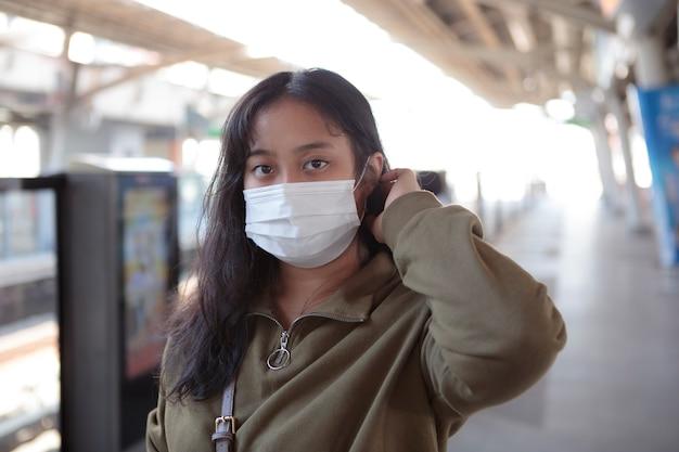 Mulher asiática usando máscara de proteção em pé ao ar livre