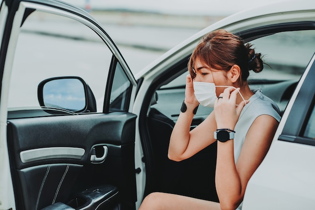Mulher asiática usando máscara de proteção facial de segurança antes de sair do carro durante a pandemia do toque de recolher por coronavírus covid-19 ao ar livre