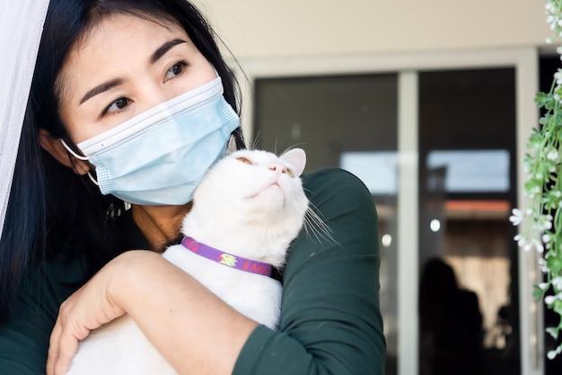 Mulher asiática usando máscara facial, auto-quarentena em casa com gato