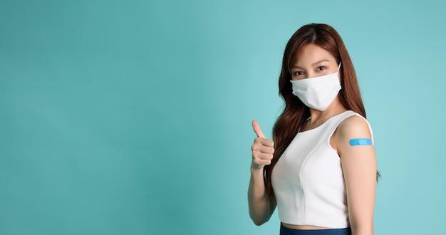 Mulher asiática usando máscara facial e mostrando os polegares para cima isolados em um fundo verde