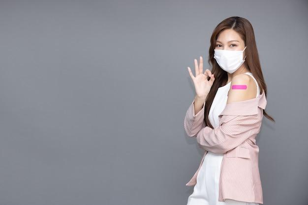 Mulher asiática usando máscara facial e mostrando sinal de ok e braço com gesso ou bandagem
