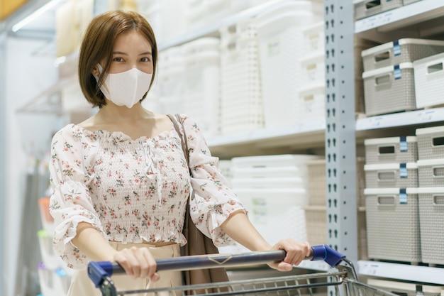 Mulher asiática usando máscara facial empurrando carrinho de compras em loja de departamentos