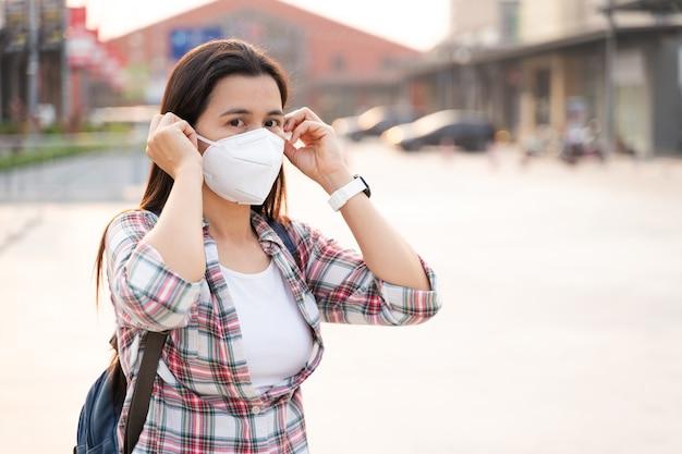 Mulher asiática usando máscara facial n95 para proteger a poluição pm2.5 e o vírus. covid-19 coronavirus e poluição do ar pm2.5 conceito médico e de saúde.