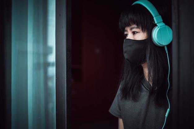 Mulher asiática usando máscara facial preta e fones de ouvido, distraída na porta e ficando em casa por distanciamento social e auto-quarentena em coronavírus ou situação de surto de covid-2019