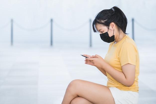 Mulher asiática usando máscara facial senta e navega nas redes sociais para atualizar as notícias da covid via celular em uma nova situação normal ao ar livre. tecnologia e conceito médico