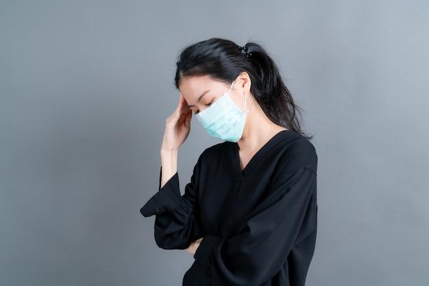Mulher asiática usando máscara médica protege a poeira do filtro antipoluição pm2.5, antipoluição e covid-19 e tem dor de cabeça na parede cinza