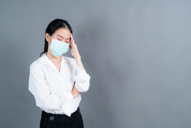 Mulher asiática usando máscara médica protege o filtro de poeira pm2.5 antipoluição, antipoluição e covid-19 e tem dor de cabeça