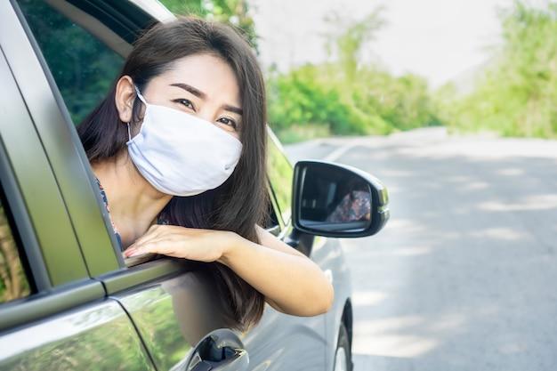 Mulher asiática usando máscara protetora em um carro e sorrindo