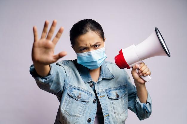 Mulher asiática usando máscara protetora, gritando com megafone isolado.