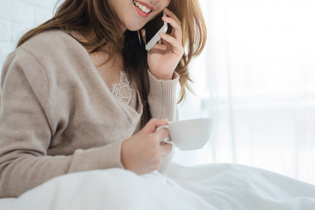 Mulher asiática usando o smartphone na cama dela, segurando a xícara de café da manhã