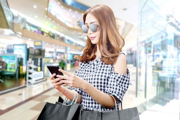 Mulher asiática, usando o telefone celular, segurando sacolas pretas no shopping