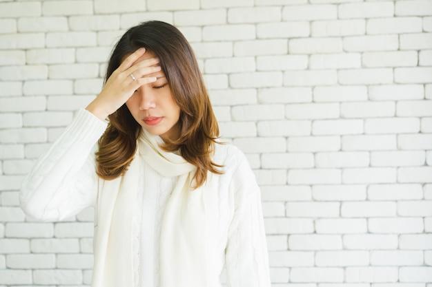 Mulher asiática usando o toque de mão e massagem na cabeça após sintoma de enxaqueca encontrado