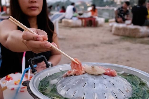 Mulher asiática usando pauzinhos para assar carne, vegetais e caldo tailandês é chamada de carne de porco - moo kra ta.