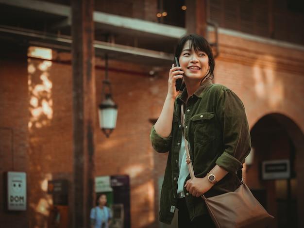 Mulher asiática usando smartphone com bom humor em shopping center