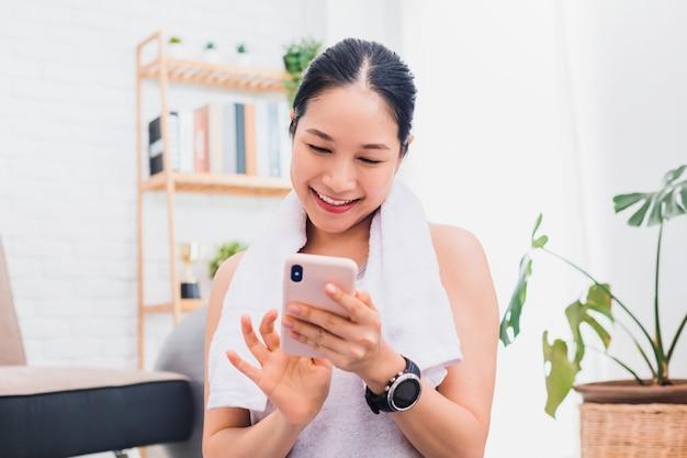 Mulher asiática usando smartphone depois de praticar ioga e fazer exercícios em casa