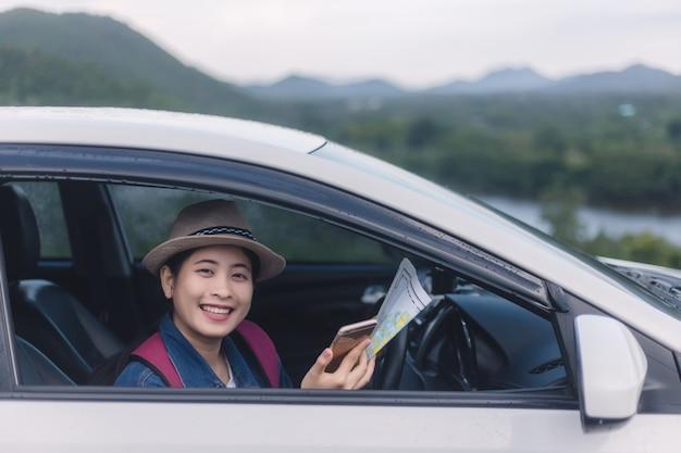 Mulher asiática usando smartphone e mapa entre dirigir carro em viagem