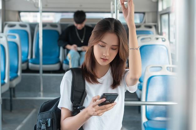 Mulher asiática usando smartphone no ônibus