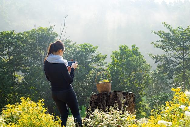 Mulher asiática usando smartphone tira foto na natureza.