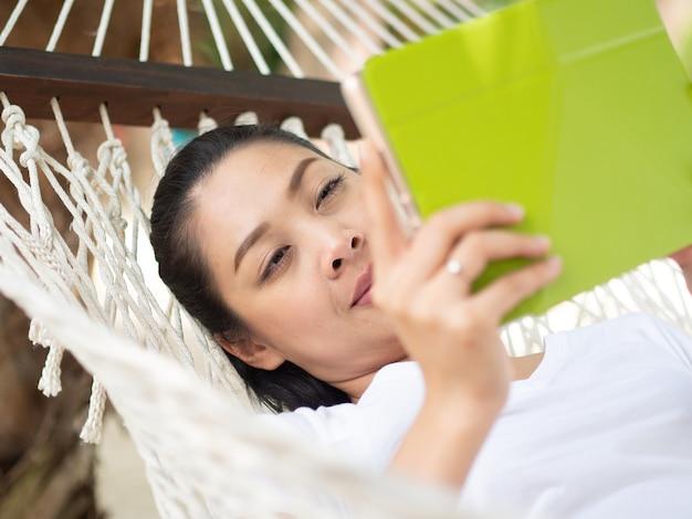 Mulher asiática usando tablet e relaxar na rede na praia na tailândia