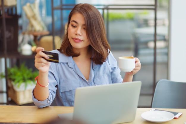 Mulher asiática, usando telefone celular com cartão de crédito e computador portátil para fazer compras de pagamento on-line no café café com amigos