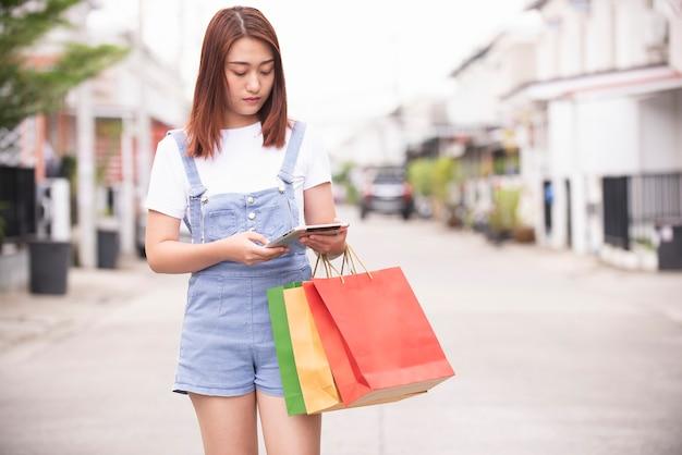 Mulher asiática usando telefone celular e carregando uma sacola colorida para compras online