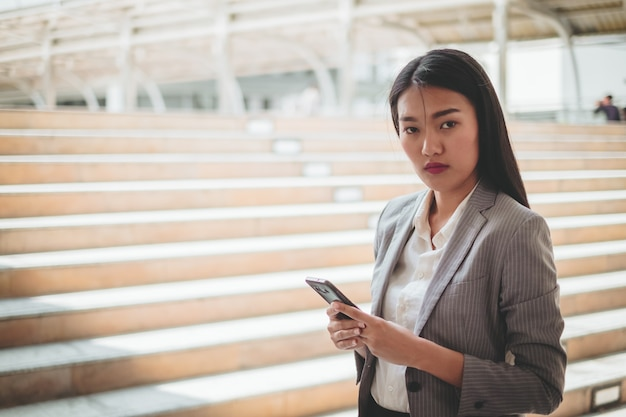 Mulher asiática usando telefone celular, smartphone no edifício da cidade
