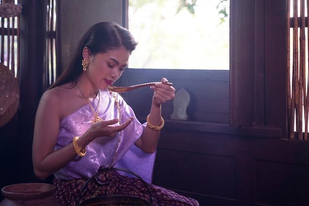 Mulher asiática usando traje tailandês tradicional de acordo com a cultura e tradição culinária na cozinha