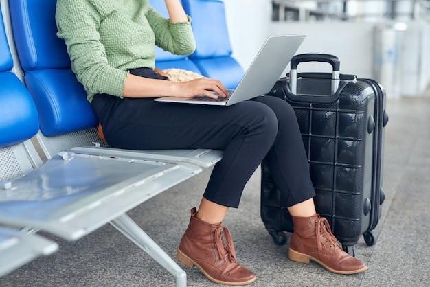 Mulher asiática usando um laptop no terminal do aeroporto sentada com uma mala de viagem para viajar