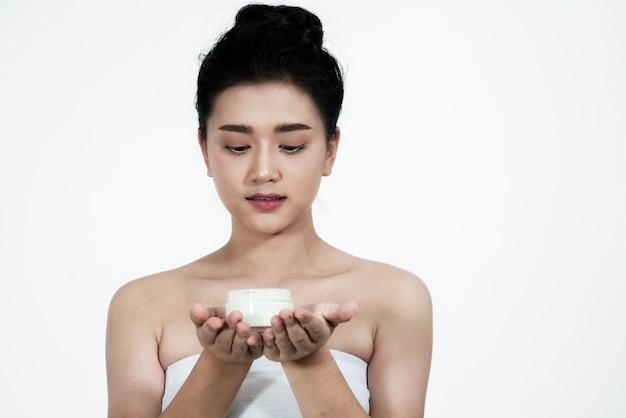 Mulher asiática usando um produto de cuidados da pele um background.girl branco está feliz com a pele crea