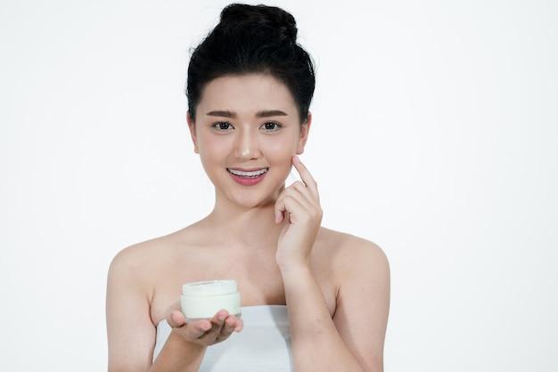 Mulher asiática usando um produto de cuidados da pele um background.girl branco está feliz com o creme de pele