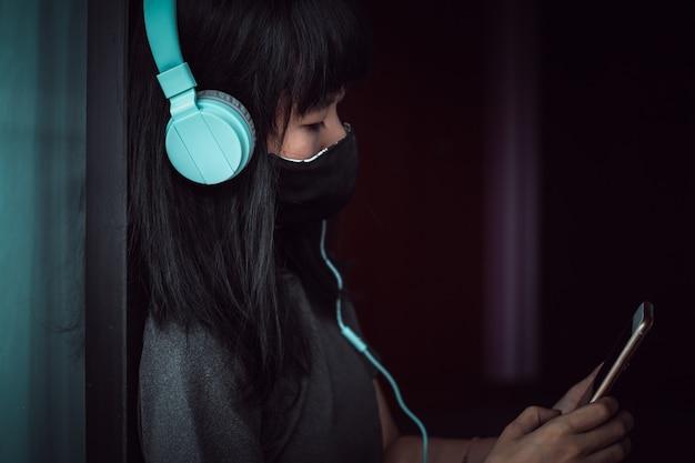 Mulher asiática usando uma máscara facial preta e fones de ouvido, usando o smartphone e ficando em casa para distanciamento individual e social em coronavírus ou conceito de situação de surto covid-2019