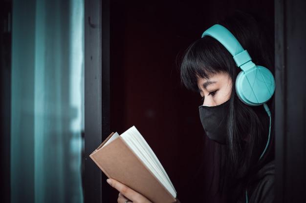 Mulher asiática usando uma máscara preta e fones de ouvido, lendo um livro e ficando em casa por distanciamento individual e social em coronavírus ou conceito de situação de surto covid-2019