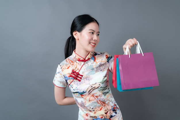Mulher asiática usando vestido tradicional chinês com a mão segurando uma sacola de compras na parede cinza