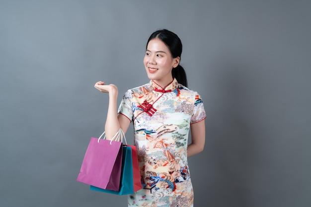 Mulher asiática usando vestido tradicional chinês com a mão segurando uma sacola de compras